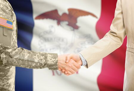 American soldier in uniform and civil man in suit shaking hands with certain USA state flag on background - Iowa Stock Photo