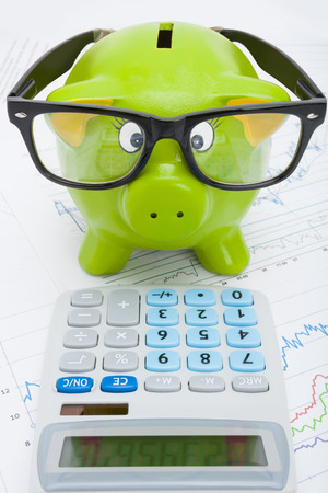 Stock market charts with piggy-bank and calculator over it