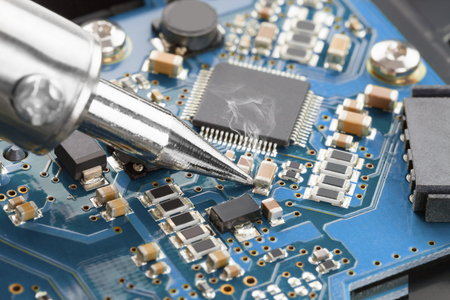 Soldering iron and blue microcircuit - close up studio shot Stock Photo