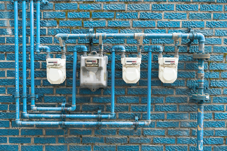varios caminos de gas colocados en una pared azul de un edificio residencial Foto de archivo