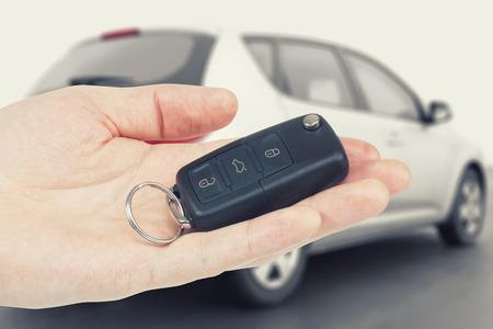 Car keys on a palm with car on background Foto de archivo