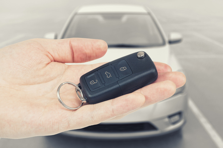 Folded car keys on a palm with car on background