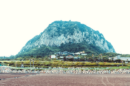 JEJU ISLAND, SOUTH KOREA - AUGUST 18, 2015: Small town located by the sea shore with big turtle shaped mountain right behind it - Jeju Island, South Korea
