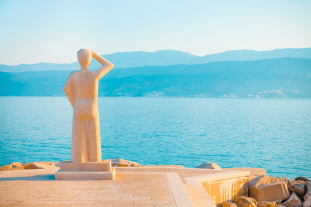 POSTIRA, CROATIA - JULY 12, 2017: Famous stone monument of person looking into a horizon in a small town Postira - Croatia, Brac island