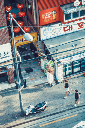 SEOUL, SOUTH KOREA - AUGUST 10, 2015: A young happy couple holding hands and passing down the street - Seoul, South Korea Редакционное