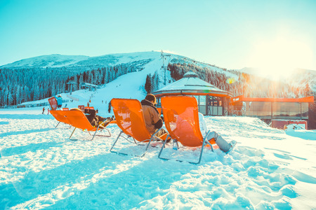 CHOPOK, SLOVAKIA - JANUARY 11, 2017: Lots of skiers relaxing in chairs near apres ski bar at Chopok downhill - Slovakia