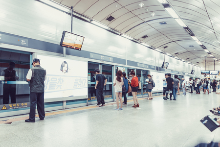 SEOUL, KOREA - AUGUST 12, 2015: Lots of different people standing in the line on a subway platform and patiently waiting for their train to come - Seoul, South Korea Редакционное