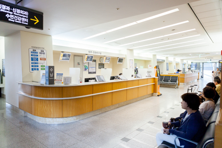 SEOUL, KOREA - AUGUST 12, 2015: Many people waiting at the registration desk of Yonsei University Cancer Hospital - very prestigious high end hospital in Seoul, South Korea