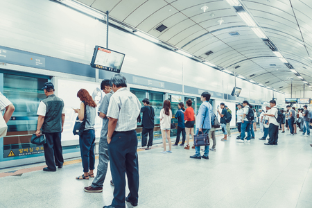 SEOUL, KOREA - AUGUST 12, 2015: Different people standing in the line on a subway platform and patiently waiting for their train to come - Seoul, South Korea