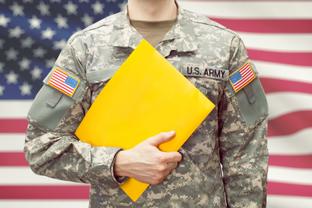 U.S. army young soldier holding yellow folder in left hand Stock Photo