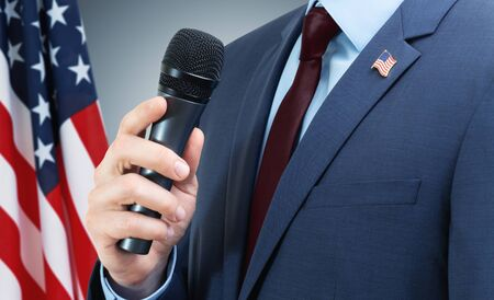 White man in suit holding microphone in hand with USA flag on background