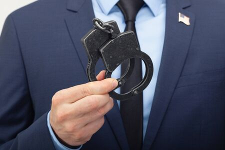 Man in suit holding handcuffs in hand with USA flag pin on his chest