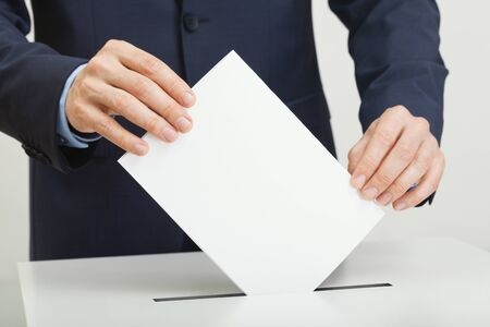 Caucasian male in suit holding ballot paper in hand and throwing it into election box Фото со стока