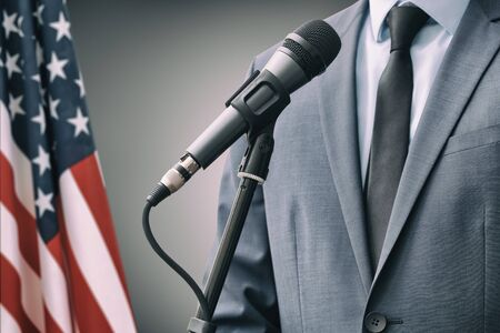 Man in suit standing next to microphone with USA flag on background