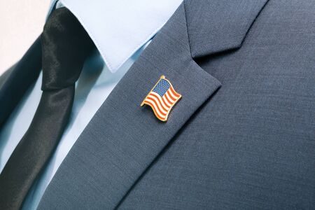 Man in suit with tie and USA flag pin at chest area