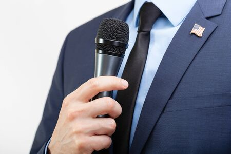 Man in suit with tie and USA flag pin on chest holding microphone in hand