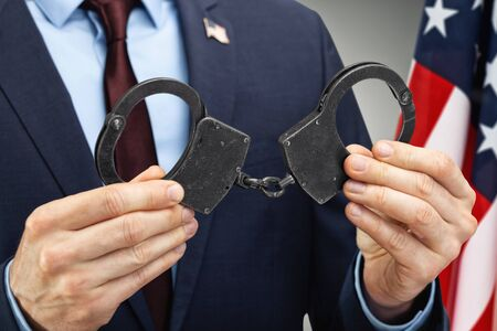 Male in suit holding black metal handcuffs with USA flag on background - close up studio shot Фото со стока