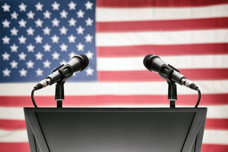 Pulpit with two microphones and USA flag on background