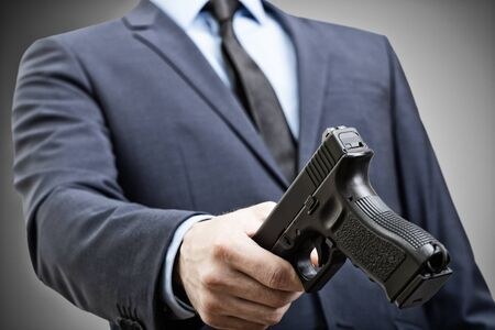White man in suit holding handgun in hand and trying to pass it to someone Фото со стока