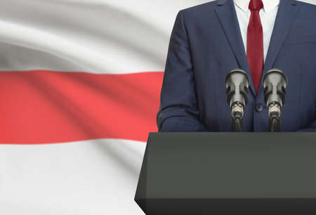 Man in suit making speech from behind the pulpit with national flag on background - Belarus Фото со стока