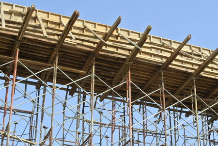 SELANGOR, MALAYSIA ? AUGUST 2014: Timber beam formwork supported by row of scaffolding in construction site in Malaysia photo