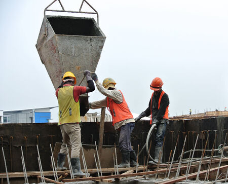 Group of construction workers casting RC wall