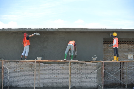 Group of skill construction workers plastering wall using cement plaster at construction site.