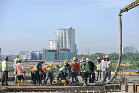 Group of Construction Workers Using Hose from Concrete Pump Editorial