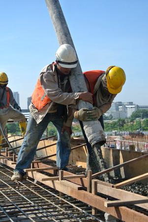 concrete pump: Construction Workers Using Hose from Concrete Pump