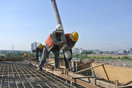 Bouwvakkers Met behulp van de Slang van Concrete Pomp
