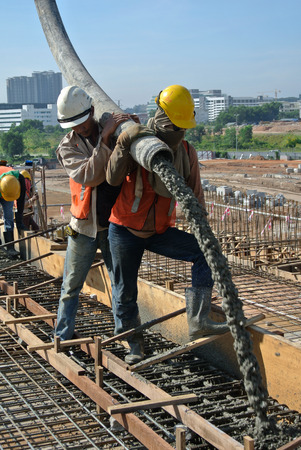 Construction Workers Using Hose from Concrete Pump