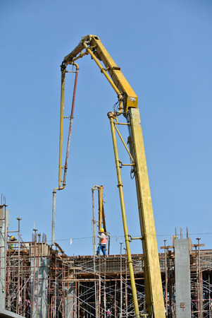 concrete pump: Construction workers using concrete pump crane with high pressure pump to move concrete from a concrete truck to the concreting site. This machine can save cost, energy and time.