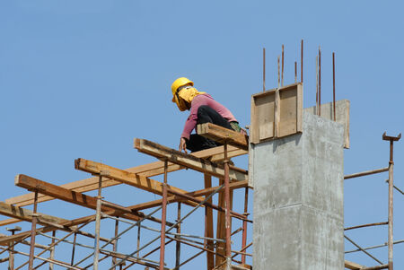 requires: A construction workers installing beam formwork. Formwork is located at the high level that requires the workers to use scaffolding. Editorial