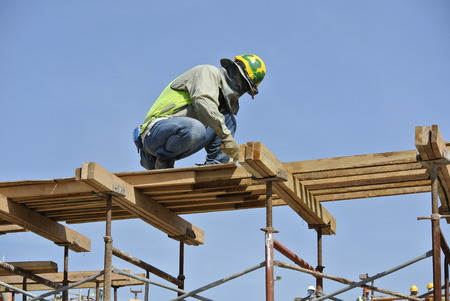 A construction workers installing beam formwork. Formwork is located at the high level that requires the workers to use scaffolding. Editorial