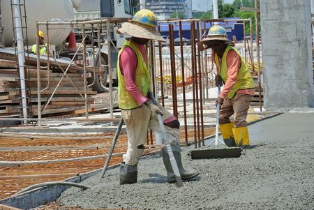 vibrator: Construction Workers Using Concrete Vibrator