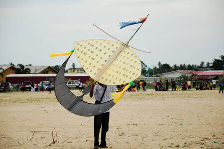 Flying Wau Bulan in Kelantan, Malaysia. Wau Bulan is one of the traditional kites that are the pride of Kelantan. Wau Bulan structure was made from bamboo and paper. photo