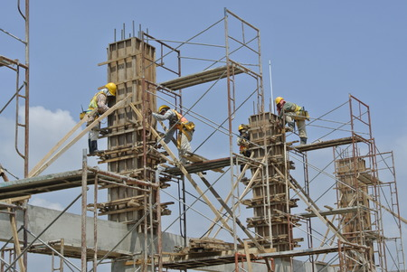 formwork: Two construction workers fabricating column formwork at construction site. They are using scaffolding as a working platform and support.