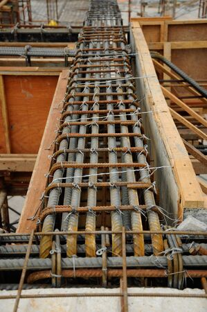 formwork: Fabrication of steel reinforcement bar for beams and timber formwork. The reinforcement bars provide strength to the concrete structure.