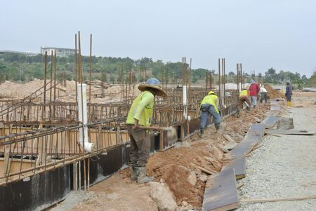 to proceed: Construction workers are installing ground beam formwork. Formwork is installed on the ground before proceed with concrete casting work.