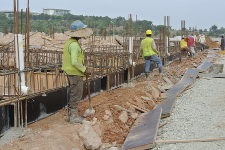 proceed: Construction workers are installing ground beam formwork. Formwork is installed on the ground before proceed with concrete casting work.