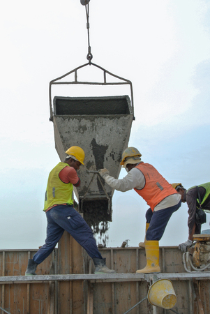 formwork: : A group of construction workers pouring concrete using concrete bucket into the timber formwork.