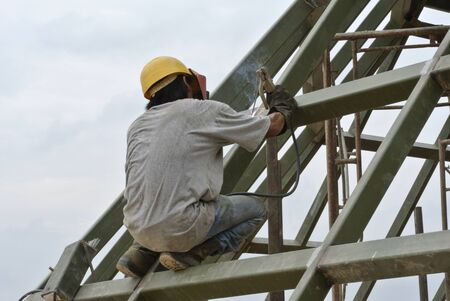 Welder wearing protective mask welding mild steel metal at the construction site on August 07, 2014 at Selangor, Malaysia. photo