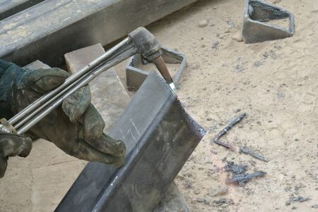 blowpipe: Workers at construction site cutting metal using blowtorch. Blowtorch produced very high temperature flame that able to cut metal in short time.