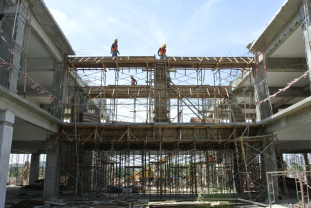 Construction workers fabricating beam formwork on July 25, 2014 at Sepang, Malaysia. Formwork is fabricated from wood and plywood.