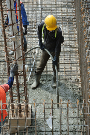 compacting: A construction worker using a concrete vibrator at a construction site in Selangor, Malaysia. Concrete vibrator is used for compacting new concrete was cast. Stock Photo