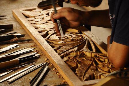 merbau: Skilled craftsman doing wood carving using traditional method