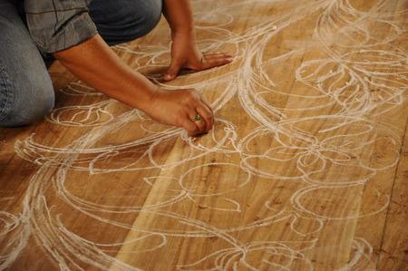 merbau: Skilled craftsman sketches their desing on wood before start carving work on November 6, 2014 at Terengganu, Malaysia. Craftsman using floral motifs as inspiration to express their creativity.
