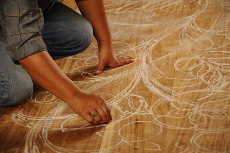 graver: Skilled craftsman sketches their desing on wood before start carving work on November 6, 2014 at Terengganu, Malaysia. Craftsman using floral motifs as inspiration to express their creativity.