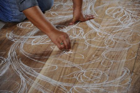 terengganu: Skilled craftsman sketches their desing on wood before start carving work on November 6, 2014 at Terengganu, Malaysia. Craftsman using floral motifs as inspiration to express their creativity.