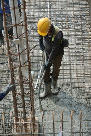 vibrator: A construction worker using a concrete vibrator at a construction site in Selangor, Malaysia. Concrete vibrator is used for compacting new concrete was cast. Stock Photo